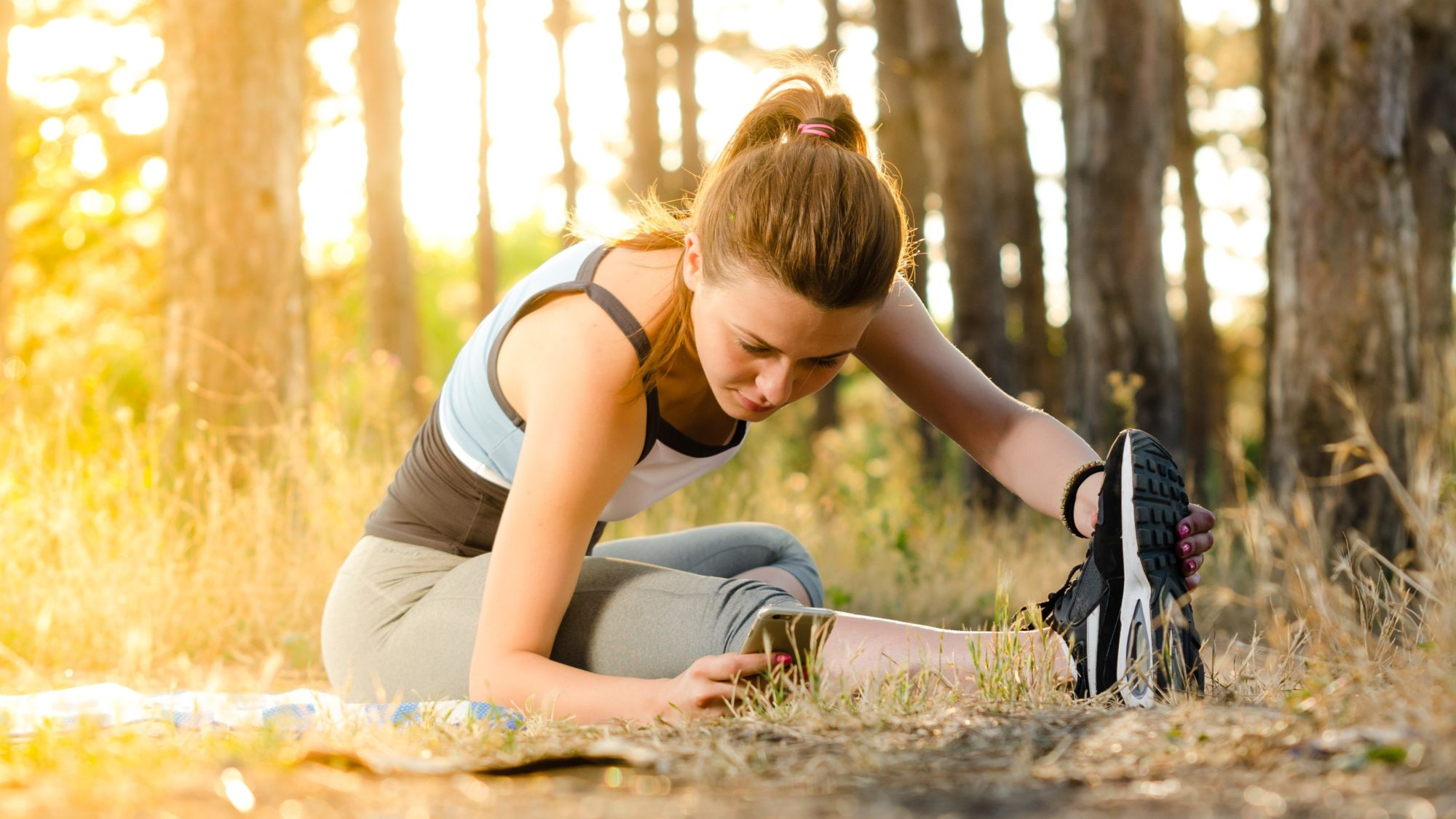 A young woman sitting down stretching her leg while reading an article on HCG and weight loss on her phone before going for a run on an outdoor trail through the woods at sunrise.