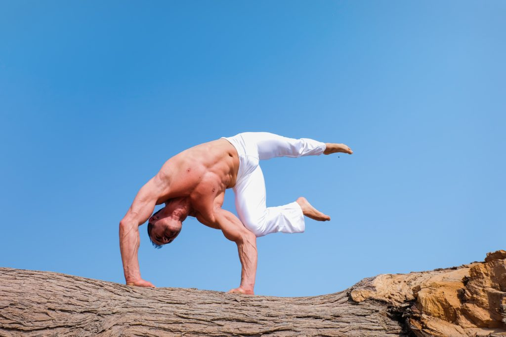 muscular man holding a yoga pose with his hands on the ground and his feet in the air