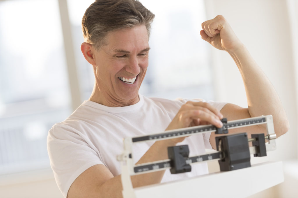 Excited mature man clenching fist while on a scale because he achieved his weight loss goal