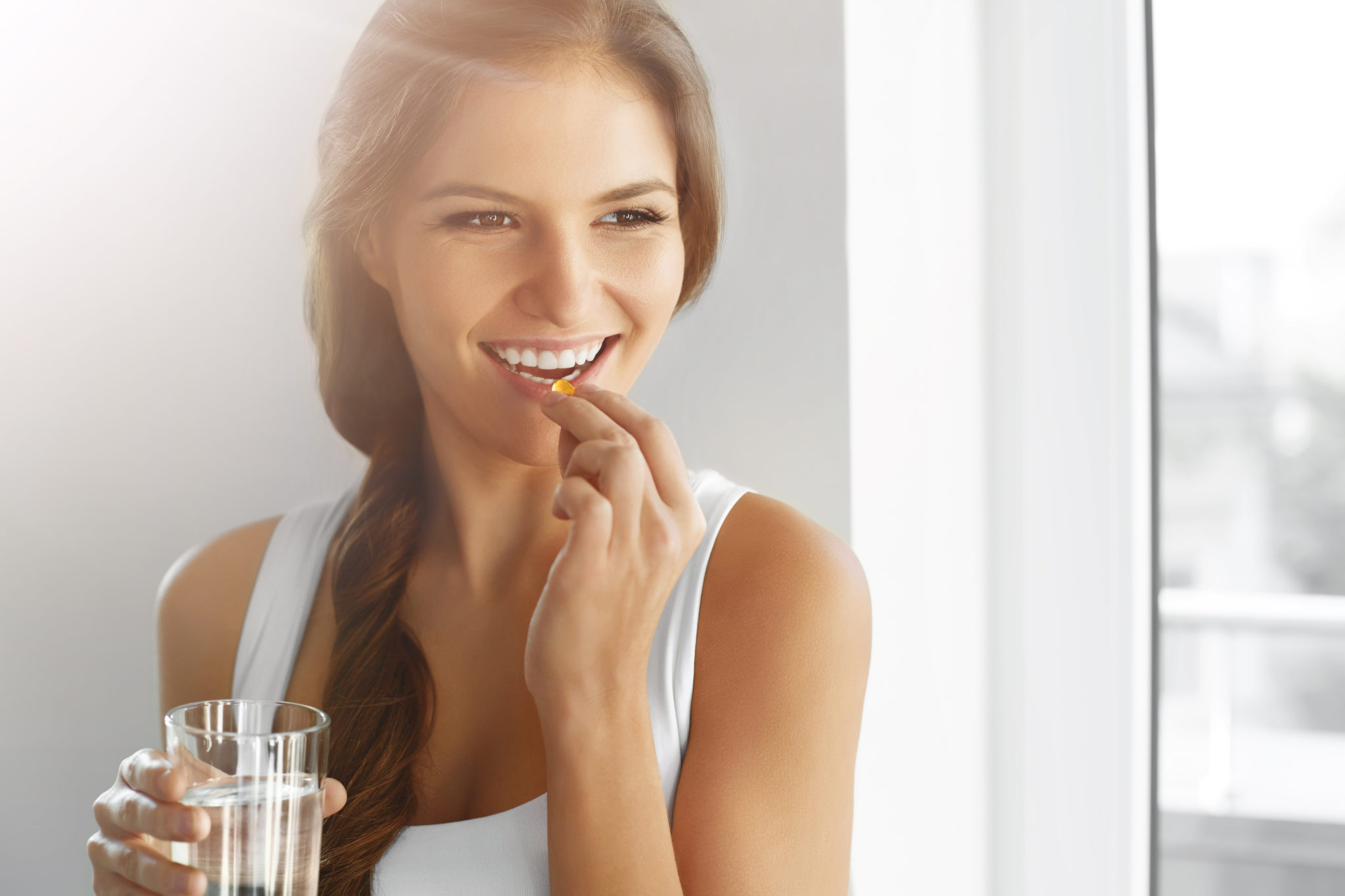 An attractive young woman taking multivitamin with a glass of water