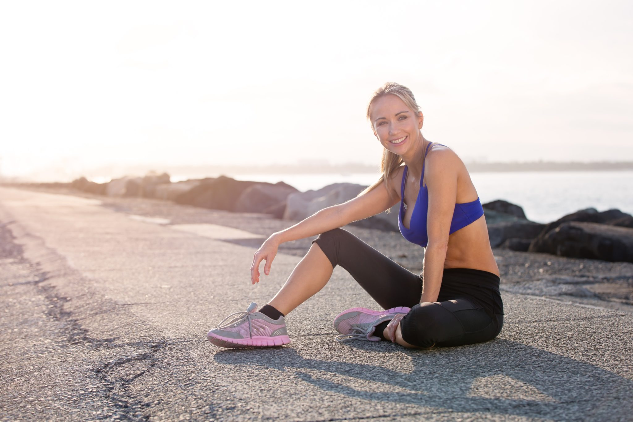 A young fit woman in workout clothes sitting down smiling