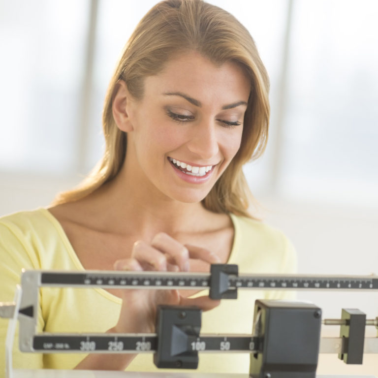 A happy young woman weighing herself on a balance scale at a weight loss clinic